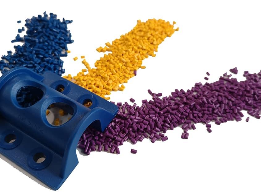 3 farbige Kunstoffteile in blau, gelb, violett zur Kunststoffverarbeitung OptiCAMMS Formenbau GmbH